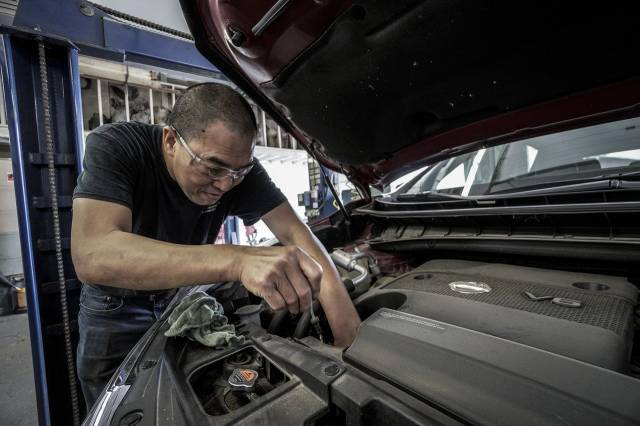 mécanicien afféré sous un capot de voiture